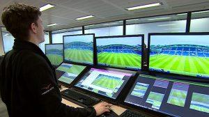 Man surveys football pitch through an array of monitors
