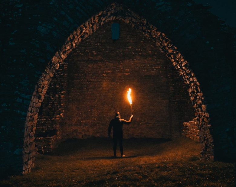 Person stands with a flaming torch at the mouth of a catacomb